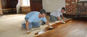 two expert floor finishers, staining a hardwood floor